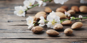 Fresh almond and flowers on the wooden table, selective focus